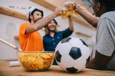 Closeup view of soccer ball and bowl with chips with group of football fans celebrating and clinking by beer glasses behind at bar stock vector