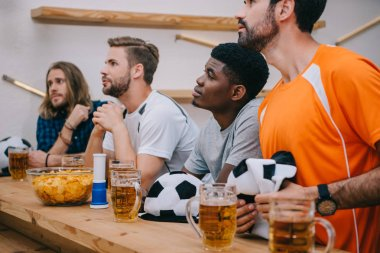 multicultural group of male football fans with soccer ball hats, fan horn, chips and beer watching soccer match at bar