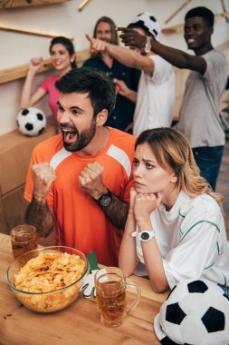 emotional multicultural football fans pointing by fingers and watching soccer match at bar with chips and beer glasses