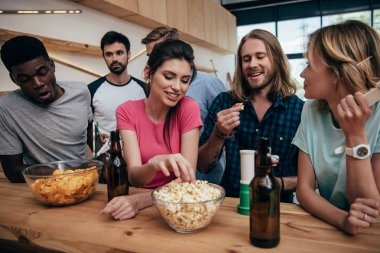 Smiling multiethnic group of friends eating popcorn and watching football match at bar stock vector