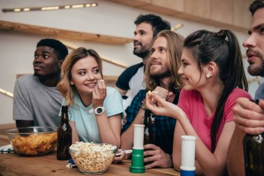 multiethnic group of friends watching football match at bar with fan horns, chips, popcorn, beer and soccer ball