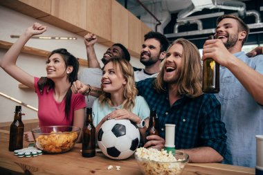 happy multiethnic group of friends celebrating, doing yes gestures and watching football match at bar with chips, beer and soccer ball