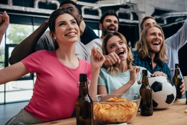 happy multiethnic group of friends celebrating and watching football match at bar with chips, beer and soccer ball