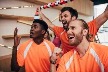 excited multicultural male football fans in orange t-shirts celebrating and gesturing during watch of soccer match at bar