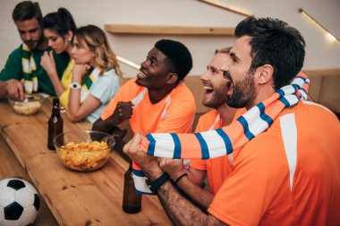side view of happy young multicultural friends in orange fan t-shirts celebrating goal in soccer match while their friends sitting upset on other side of bar counter