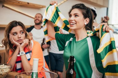 happy young woman in green fan t-shirt and fan scarf celebrating while her upset female friend in orange t-shirt sitting during watch of soccer match at bar