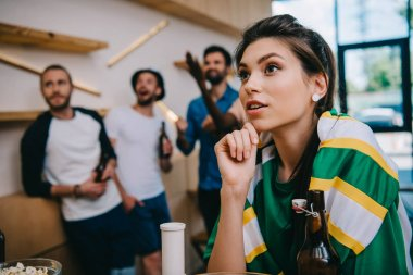 woman in green fan t-shirt and fan scarf  and her male friends standing behind during watch of soccer match at bar