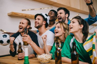 excited multicultural friends with beer bottles doing yes gestures during watch of soccer match at bar