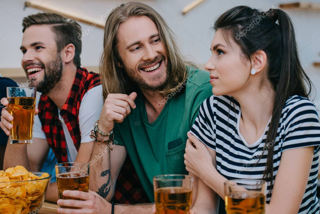 smiling group of friends drinking beer and watching football match at bar