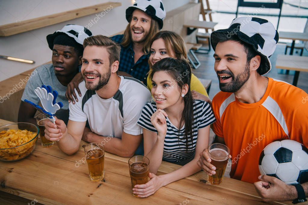 happy multicultural group of friends in soccer ball hats drinking beer and watching football match at bar