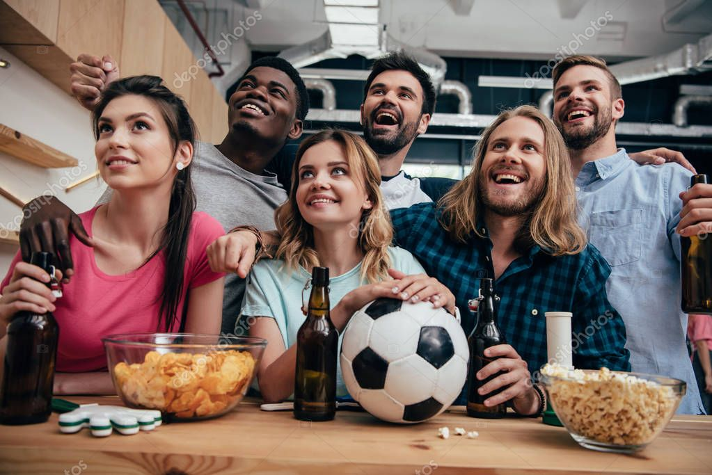 smiling multiethnic group of friends watching football match at bar with chips, popcorn, beer and soccer ball