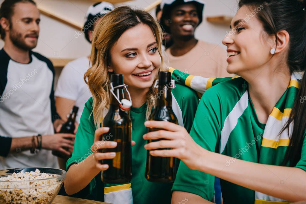 smiling young women clinking beer bottles and their male friends standing behind during watch of soccer match at bar