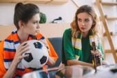 Fényképek két női futball rajongók különböző rajongó pólók labda és a sör üveg néztek egymásra, otthon