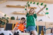 Fényképek fiatal mosolygó nő zöld rajongó póló ünneplése győzelem és a gazdaság több mint ideges női barátom narancssárga póló néz foci közben mögött ül míg Törzsegyezés sál otthon