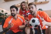 emocionální mladých mužských fotbalových fanoušků v oranžová trička s míčem a popcorn sledovat fotbalový zápas doma