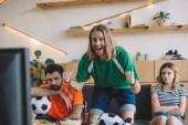 Fényképek boldog fiatalember a zöld rajongó póló ünnepelte, míg ő ideges meg mögött ülve a kanapé alatt néz foci meccs otthon