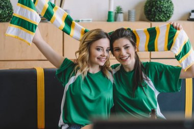 smiling female football fans in green t-shirts and scarf celebrating during watch of soccer match at home