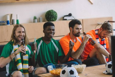 smiling football fans in green t-shirts celebrating while their upset friends in orange t-shirts sitting near on sofa during watch of soccer match at home