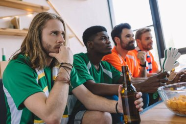 focused group of multicultural male friends in different fan t-shirts watching soccer match at home