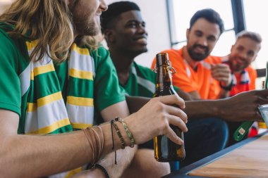 cropped shot of man in green fan t-shirt and scarf holding beer bottle while his multicultural male friends watching football match at home