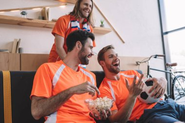 smiling male football fans in orange t-shirts with ball and popcorn watching soccer match at home