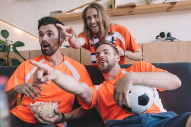 young male football fans in orange t-shirts pointing by fingers to shocked friend with popcorn during watch of soccer match at home
