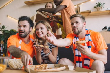 young man pointing by hand and his friends eating pizza and watching soccer match at home