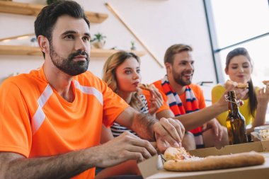 young man taking pizza slice from box while his friends eating pizza and watching soccer match at home
