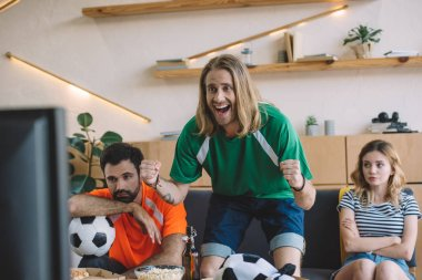 happy young man in green fan t-shirt celebrating while his upset friends sitting behind on sofa during watch of soccer match at home