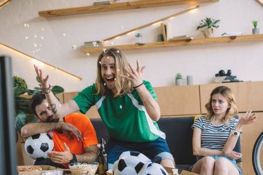 excited young man in green fan t-shirt throwing popcorn and celebrating while his upset friends sitting and gesturing behind on sofa during watch of soccer match at home