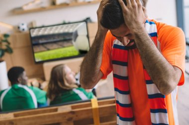 upset young man in orange t-shirt and scarf holding hands on head while his friends watching soccer match on tv screen at home