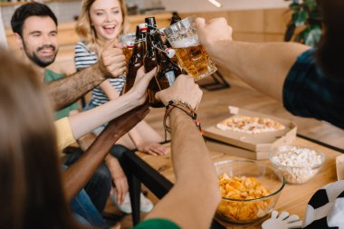 cropped shot of soccer fans celebrating victory and clinking beer bottles and glasses over table with pizza, popcorn and chips at home