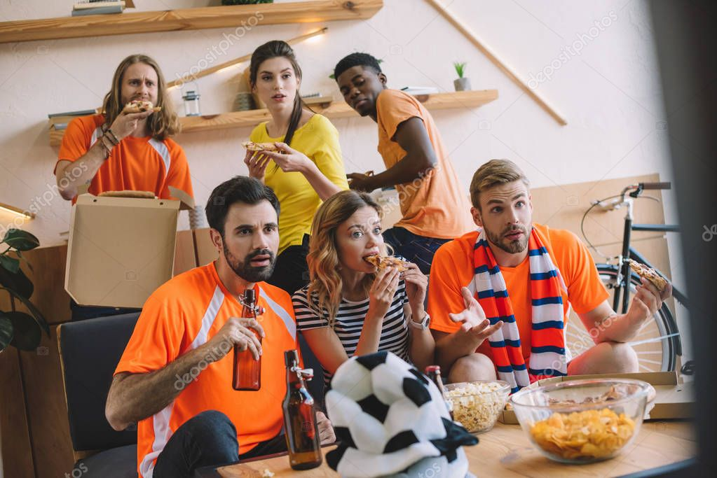 multicultural friends with pizza and beer watching soccer match at home