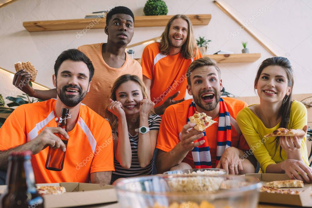 group of multicultural friends with pizza and beer watching soccer game at home