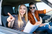 fiatal nő térképpel a kézben mutató ujját mosolygó barátja autó volán mögé ül