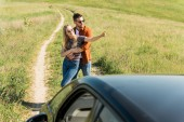 man embracing stylish girlfriend in sunglasses pointing by finger in rural field near car