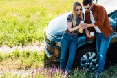 Fotografie elevated view of stylish couple with coffee cups looking at smartphone screen near car