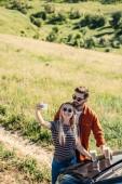 Fotografia vista di alto angolo di coppie alla moda in occhiali da sole con tazze di caffè prendendo selfie su smartphone near auto sul prato rurale