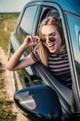 Fotografie čelní pohled nadšený mladá žena vyklání z okna auta