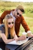 stílusos pár turista papír csésze kávé keres hely közelében autó vidéki mező megjelenítése