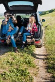Photo stylish male tourist looking through binoculars while his smiling girlfriend sitting near with coffee cup on car trunk in field
