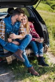 Photo stylish male traveler with binoculars and his smiling girlfriend sitting near with coffee cup on car trunk in field