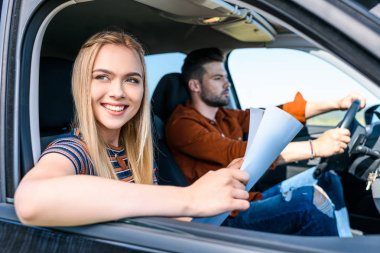 young smiling woman sitting with map in hands while her boyfriend driving car
