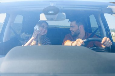 front view of smiling woman talking on smartphone and looking at boyfriend driving car