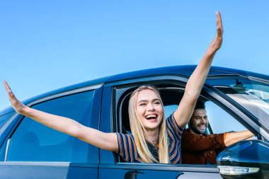 happy young woman with wide arms leaning out from car window while her boyfriend driving car