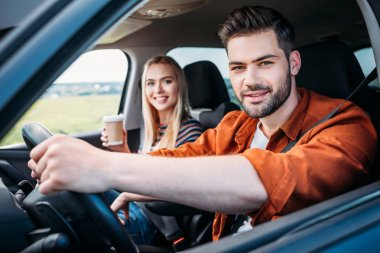 Portrait of young man sitting behind car wheel and his girlfriend with paper cup of coffee stock vector