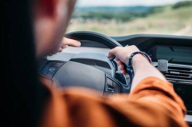 cropped image of man sitting behind his car wheel