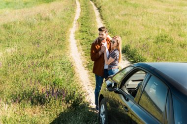 elevated view of young stylish couple embracing near car in rural field