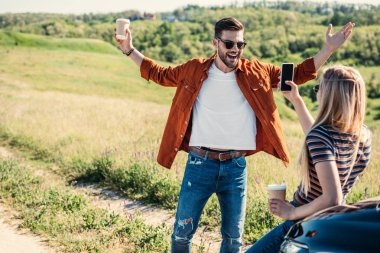 rear view of woman taking picture of boyfriend with wide arms holding coffee cup near on rural meadow