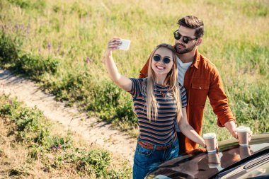 elevated view of stylish couple in sunglasses with coffee cups taking selfie on smartphone near car on rural meadow